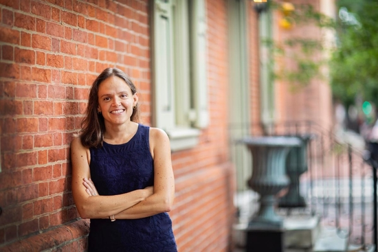 Professor Francesca Russello Ammon leans against a brick rowhouse