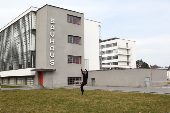 "Student dancing on lawn in front of building with large sign saying ""Bauhaus""."