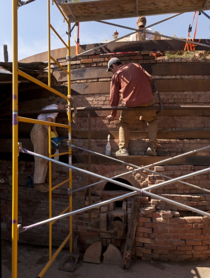 People sitting of scaffolding working on a structure made of bricks.
