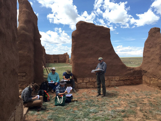 Conservation team sitting amongst adobe ruins at fort union