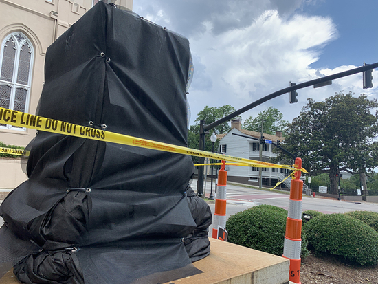 A black tarp covers a pedestal surrounded by CAUTION tape