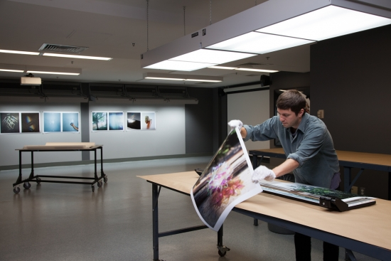 Student prepares to trim a large photograph in a softly lit studio. Large prints of photographs hang on the wall in the back