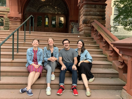 Four members of PPSA sitting and smiling on the steps of Fisher