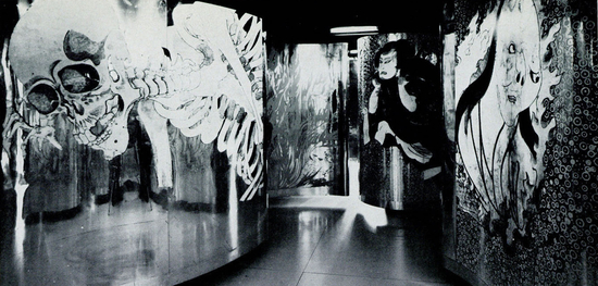 B&W photo of winding mural labyrinth featuring a collage of traditional Japanese paintings of samurai and folklore monsters