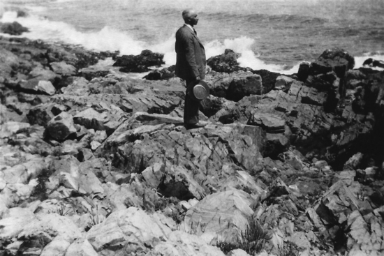 A middle aged man in a business suit stands on a rocky shore, looking at the ocean