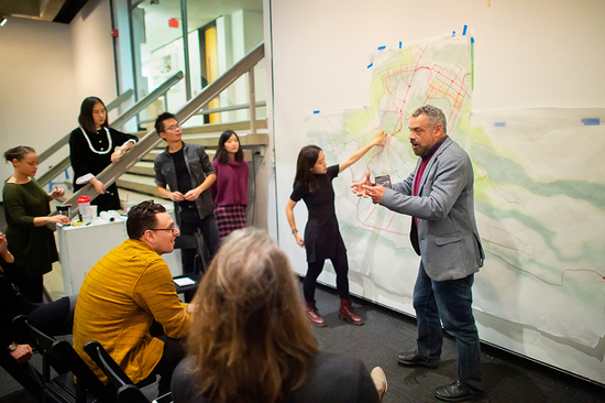 A studio instructor addresses students and critics in front of a landscape rendering