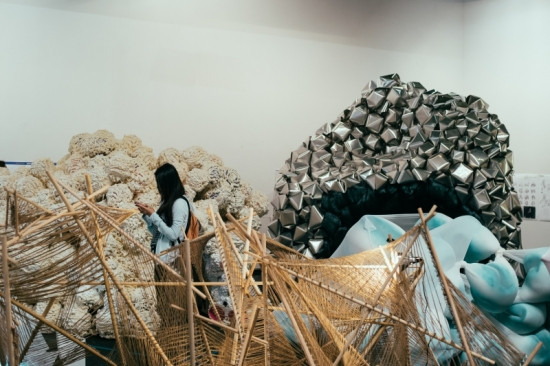 Collection of large abstract sculptures and one woman examining them.
