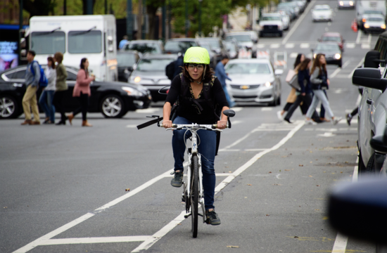 Megan Ryerson wears a helmet outfitted with clear eye-tracking glasses as she travels in a bike lane on a Philly street