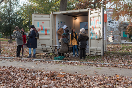 Students holding an information booth in a small cargo container during fall