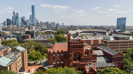 Ornate red brick building next to brutalist building with Philly skyline in distance