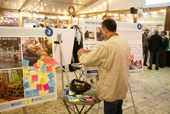 Man putting sticky notes on a poster board in a large conference space