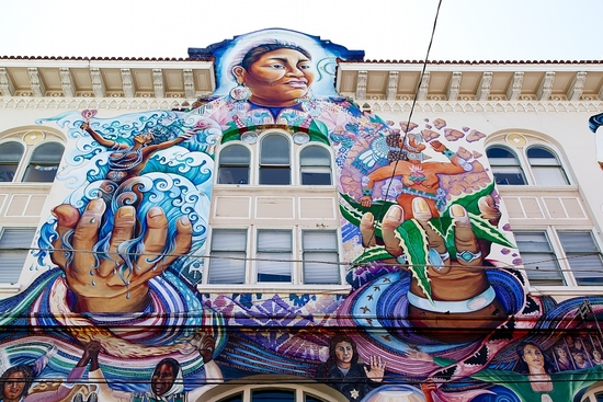 Multicolor mural depicting a smiling woman holding animated figures