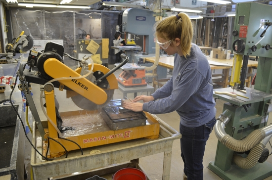 Student working with a piece of heavy cutting machinery.