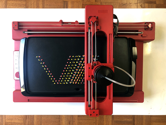 A V-shaped array of rainbow colored dots on black griddle with a red robotic arm above