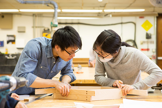 Two students working together on a wooden frame a studio