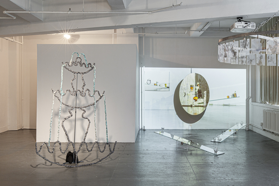 white gallery space featuring student work including projections and sculptures