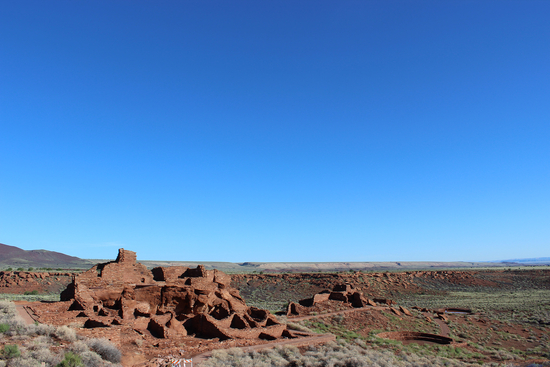 A cluster of red earthen structures under expanse of blue sky in the desert