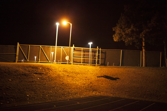 Outdoor art piece featuring a shadow cast by a streetlight that looks like a person.