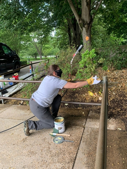 Jennifer Boggs applies hot wax to the bronze railings at Arlington National Cemetery.