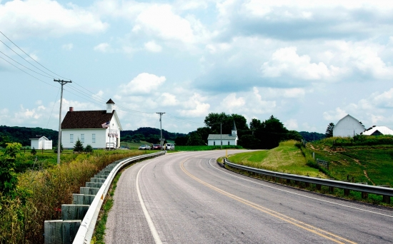 Photograph of section of highway and several houses representing classic American architecture.