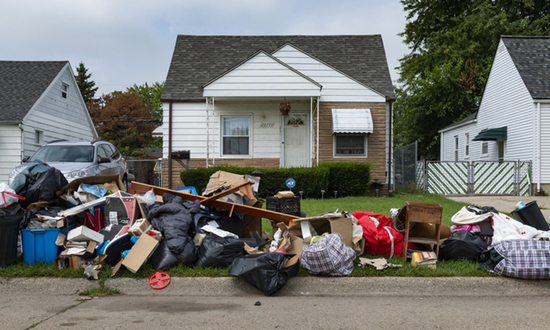 Piles of trash and furniture left on the curb in front of a small house