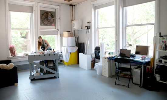 In a large studio space with large windows a student works at a work table in the middle of the room