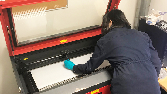 A person cuts plastic using a laser cutter
