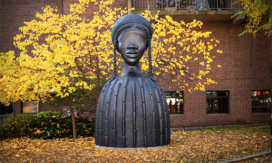 Large bronze sculpture of a woman seen against autumn trees