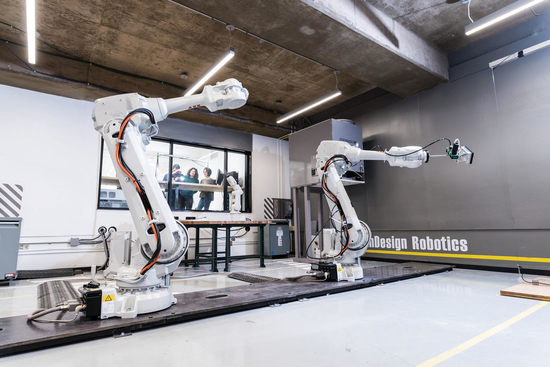 Two large robotic arms in a studio with students viewing them through a window to an adjacent room