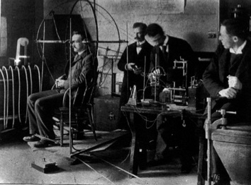 Old black and white photo of group of men performing artistic and psychological experiments.