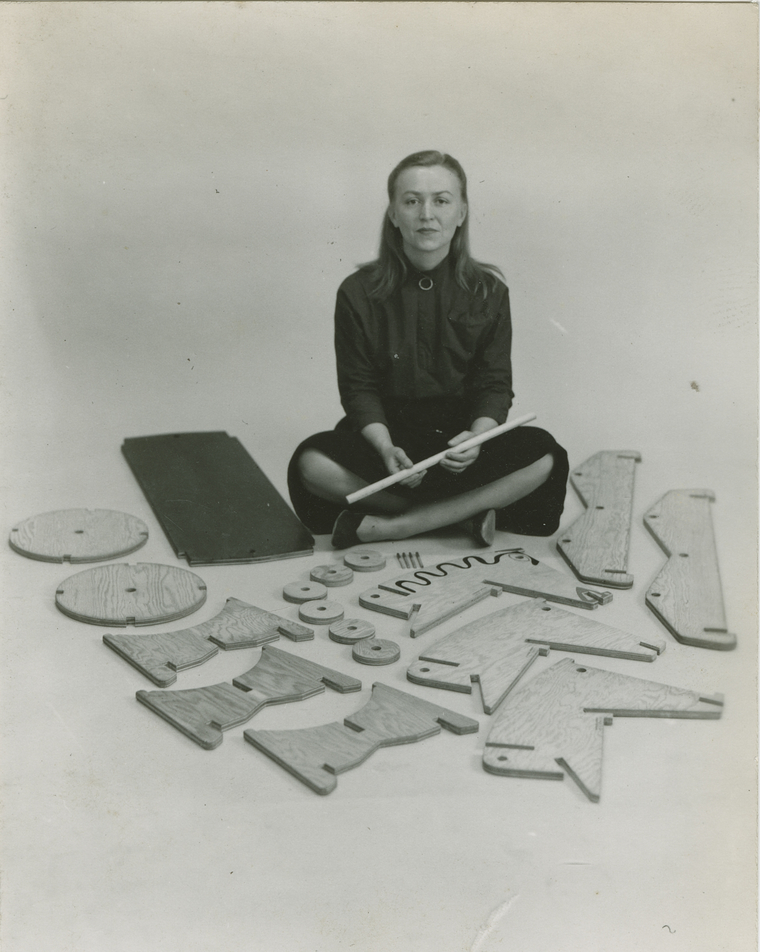 Anne Griswold Tyng sitting on floor surrounded by wooden cutouts