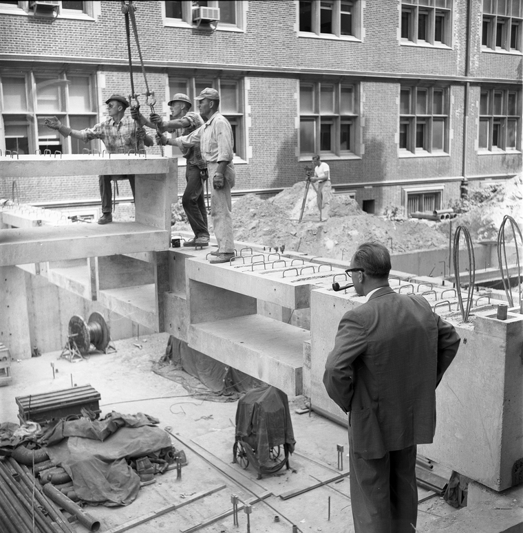 B/W photo of men working at construction site with other man watching them while smoking a pipe