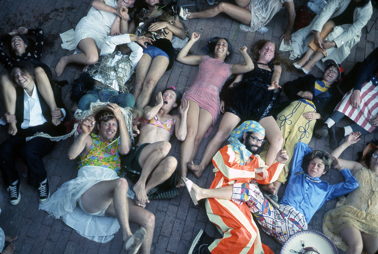 lots of people in strange clothing lying on floor smiling at the camera above them