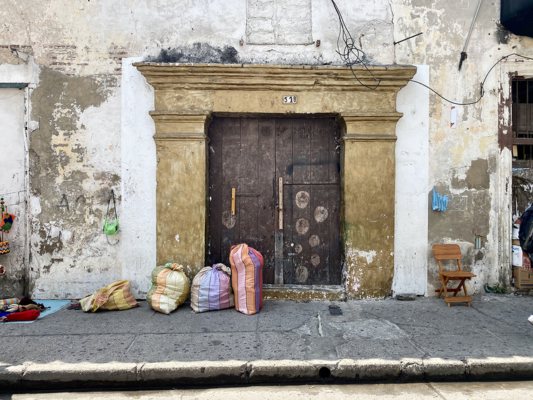 Photo of an old door with packages set on the ground