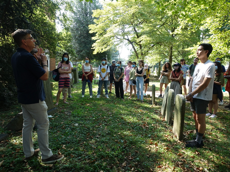 Students gather for lecture in lush green cemetery