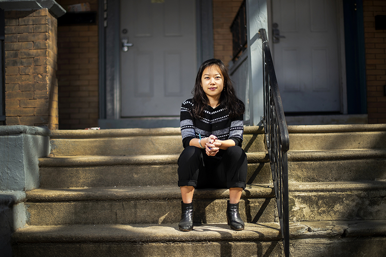 Lily Cheng sitting on the steps going up to the front porch of her house