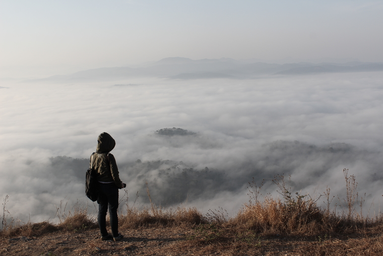 Student on mountain overlooking clouds below