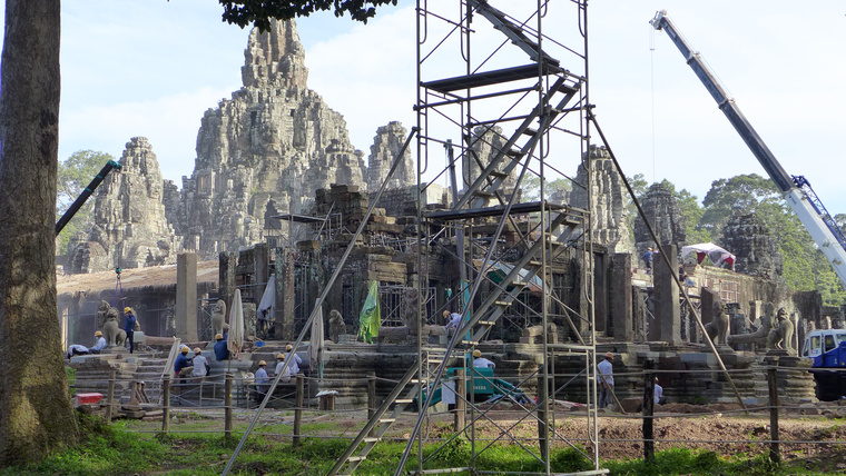 Workers in hard hats operate machinery at a stone temple