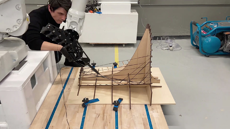 A man watches a robot arm weave black fibers on a wood frame