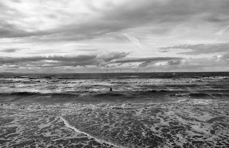 Black and white photo of an ocean coast with a sculpture of a man in the waves