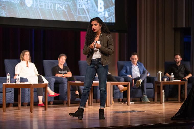Varshini Prakash on stage at Irvine Auditorium with four speakers seated behind.