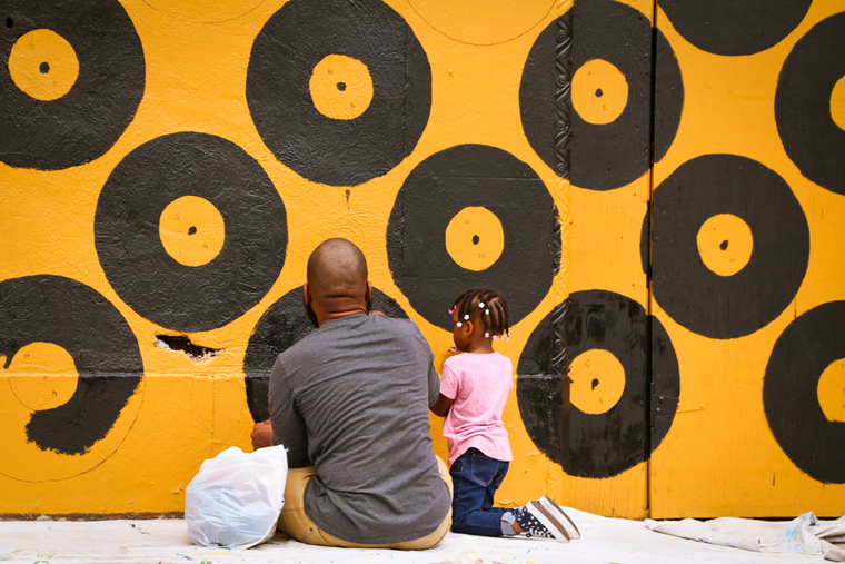 An African American man and young girl seated in front of a black and gold mural