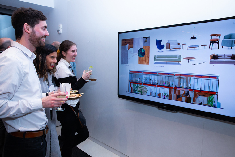 Students holding food and beverages smiling and looking at a digital display of architectural designs