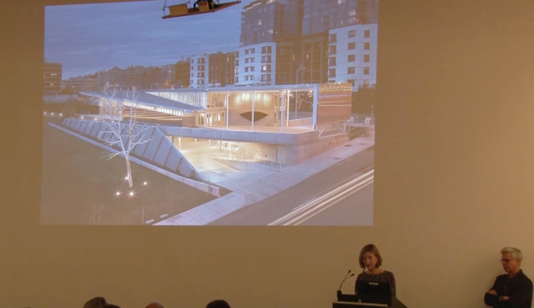 Woman giving presentation with projection in the background