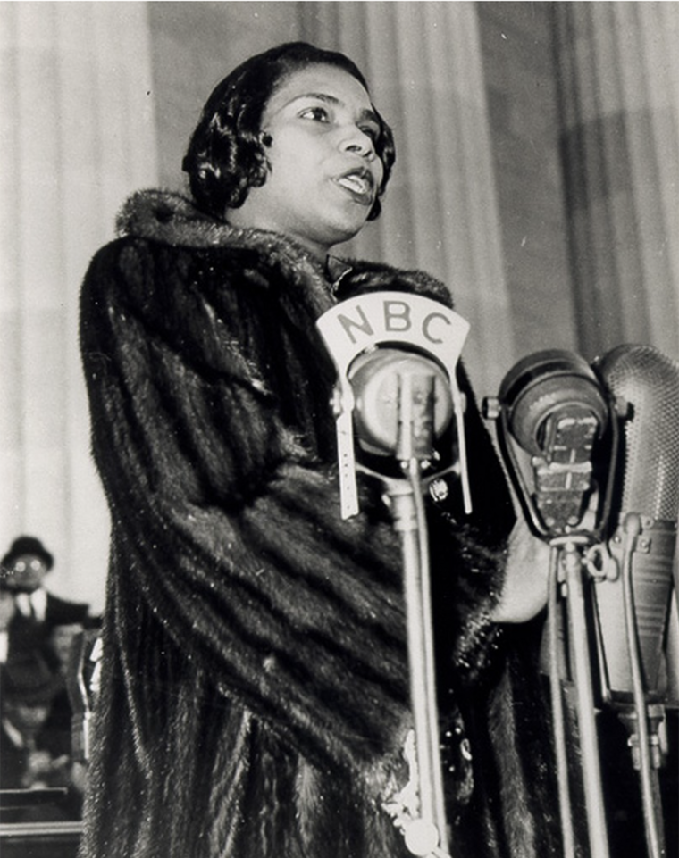 A young Black woman in a fur coat sings at a microphone
