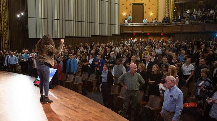 People at auditorium stand and cheer for a young woman speaking on stage