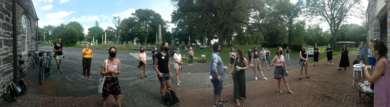 panoramic photograph of students, masked, in a cemetery.