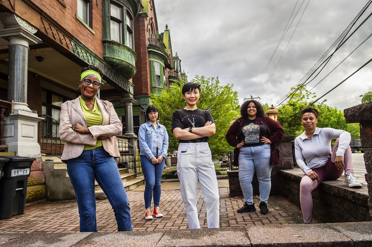 A group of women of various ages and ethnicities pose on the sidewalk outside a victorian home