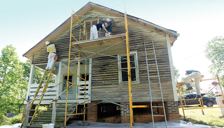 White wooden sided two story home with workers on scaffolding in front