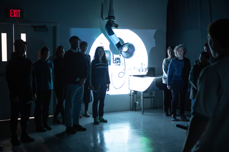 Students and Sharon Hayes stand in a darkened room
